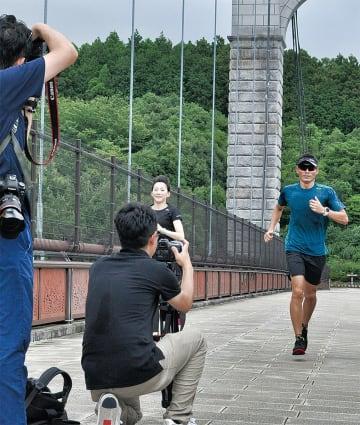 風の吊り橋で撮影に参加する青山さん(右)