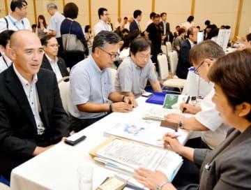 大学の就職担当者(右)に自社をアピールする企業の担当者=12日午後、松山市南堀端町