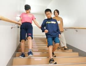 アイマスク着用した児童(左)を誘導しながら階段を降りるガイド役の児童(中)