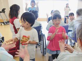 患者と手遊びする東町保育所の年長児たち