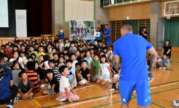 交通安全クイズの答えを発表するスミス選手(手前)に注目する児童ら=柏市