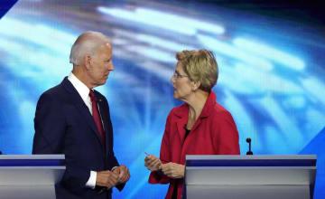 12日、米民主党の第3回候補者討論会でバイデン前副大統領(左)と話すウォーレン上院議員=テキサス州ヒューストン(ロイター=共同)