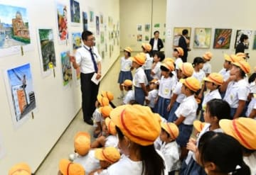 学芸員による作品解説を聞く名山小学校の生徒ら=13日午前、鹿児島市立美術館