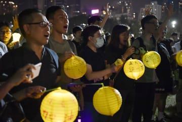 中秋節に合わせて行われた抗議活動で、メッセージが書かれた灯籠を手に歌う人たち=13日、香港(共同)