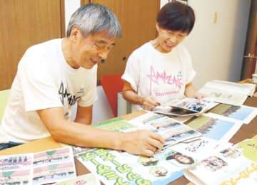 過去の大会の写真などを自宅で眺める岡島俊樹さん(左)と幸子さん