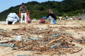 柱島の海岸に漂着したカキパイプなどのごみを拾い集める養殖業者