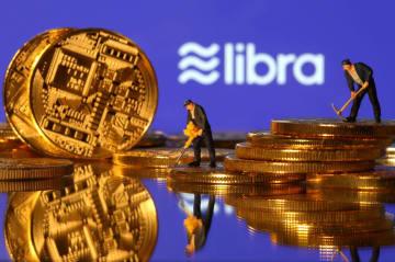 米フェイスブックが計画するリブラのロゴと、暗号資産(仮想通貨)を模した硬貨を採掘する人形=6月(ロイター=共同)