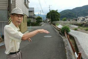 自宅前を流れる津久見川の改良復旧工事について語る丹羽新吉さん。川の拡幅で立ち退く住民もおり、「ご近所さんがいなくなるのは寂しい」と話す=13日午後、津久見市大友町