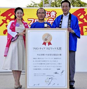 野崎町長(右)と津吹さん(左)から記念のパネルなどを受けた栗崎会長