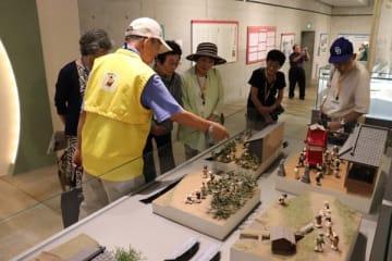 【ボランティア(左)の案内で、館内の展示品に見入る受講生ら=愛知県半田市の新美南吉記念館で】