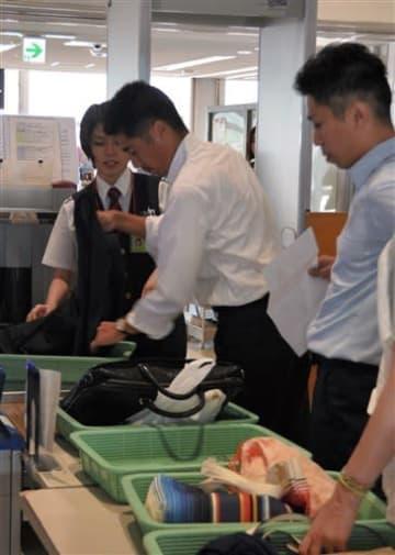 熊本空港の保安検査場で、ジャケットを脱いでトレーに乗せる男性(左から2人目)=13日、益城町
