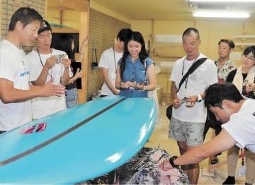 室原さん(左)からサーフボード製造過程を学ぶツアー参加者