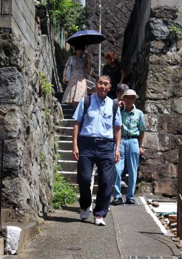 参加者と一緒に被爆した場所を歩く中村さん=長崎市緑町