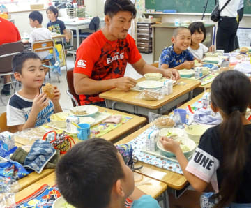 杉永亮太選手(中央)と笑顔でロシア料理をほおばる児童=横浜市旭区の市立四季の森小学校