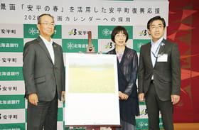 「安平町の春」が描かれたカレンダーを囲む(左から)笹原頭取、佐藤さん、及川町長