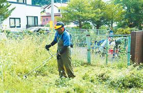 来年3月の開館を目指して、丁寧に草を刈り取る地区連関係者
