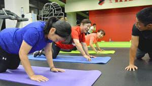 鈴木パフォーマンスコーチ(右)の指導でサーキットトレーニングに励む参加者