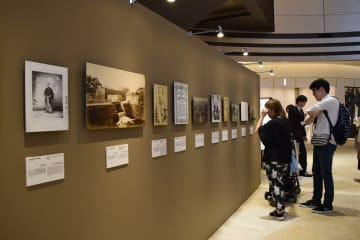東京で開催している写真展初日、第1章「出会い」の展示物と鑑賞する入場者の様子=14日
