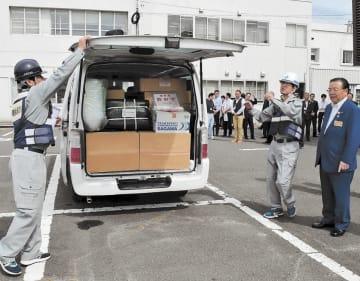 支援物資をバンに積み込み、千葉県君津市へ出発する村松危機管理監(左)ら