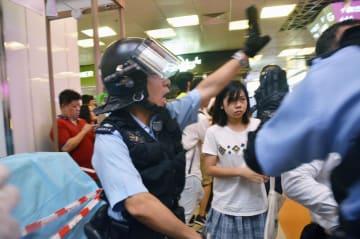 14日、香港・九竜地区のショッピングモール内で起きた若者らと親中派市民の衝突をおさめようとする警官(共同)