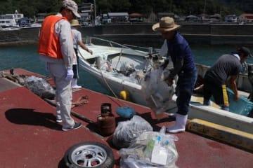 集めたごみを船から漁港に降ろす漁業者ら=笠岡市神島外浦