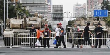 軍事パレードの予行演習のため、北京市内で待機する戦車などの装甲車両。道路が封鎖され、立ち往生する市民の姿も見られた=14日(共同)