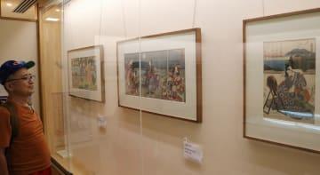月が描かれた浮世絵に見入る来場者 =秦野市平沢の「はだの浮世絵ギャラリー」