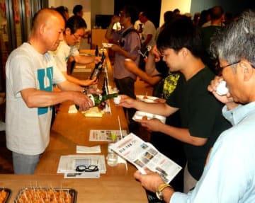 訪れた人に広島の酒をつぐ蔵元関係者(左側)