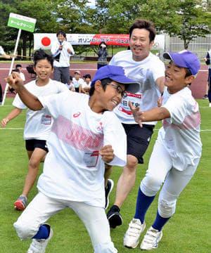 本田さんらオリンピアンと一緒に体を動かす子どもたち=福島市・あづま総合運動公園補助陸上競技場