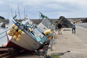 強風で大きく傾いた漁船=13日午後2時、鋸南町勝山