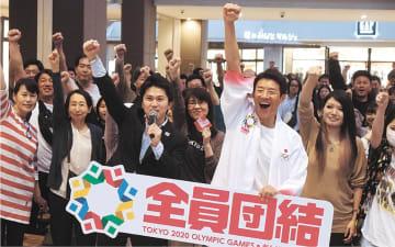 集まった約400人と拳を突き上げる松岡さんと千田さん(中央左)