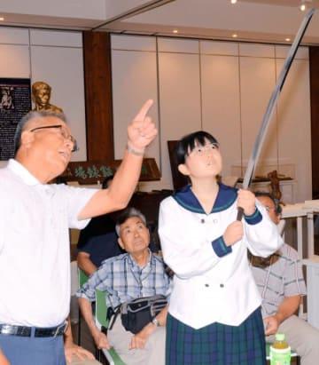 高校生(右)に日本刀を手にしてもらい、鑑賞方法を伝える近藤さん
