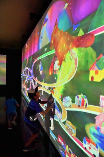 自分で描いた車などが画面を走る「お絵かきタウン」に怪獣が出現し、ビームで退治する子ども=14日、釜石市港町