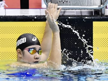 成年女子100メートル背泳ぎで優勝し、歓声に応える兵庫・白井璃緒=山新スイミングアリーナ