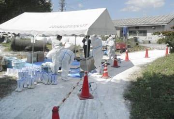 長野県塩尻市の県畜産試験場の敷地内で作業を終え、防護服を着替える作業員=15日(同県農政部提供)