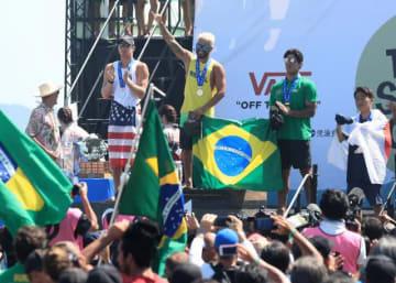表彰台に立ち右手を突き上げる優勝したイタロ・フェヘイラ(中央)と、日の丸の旗を背に巻く4位の村上舜(右端)ら=15日午後、宮崎市・木崎浜