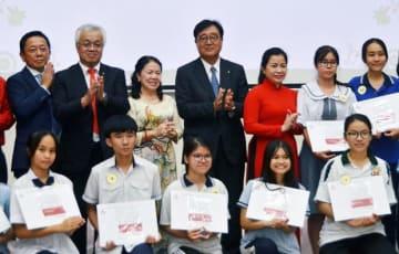 三菱モーターズ・ベトナム(MMV)25周年イベントに合わせて実施した奨学金支援の授与式典に、三菱自動車の益子会長(後段中央)とMMVの堀之内社長(後段左から2人目)も臨席した=12日、ホーチミン市