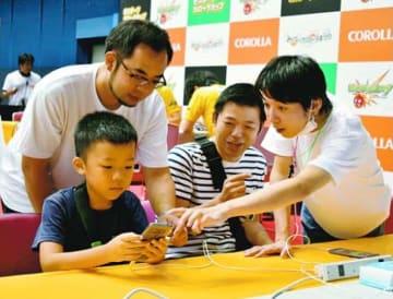 初心者や子どもに操作方法を教える「国府」のメンバー(右)=徳島市のアスティとくしま