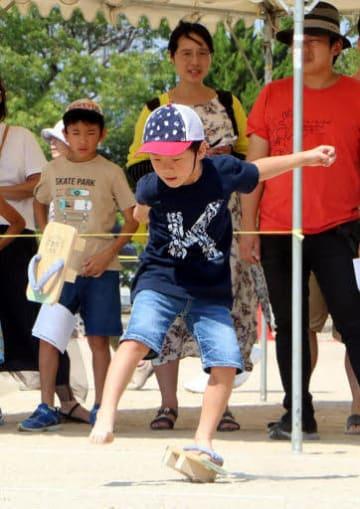ゲタを蹴り飛ばす競技に挑戦する子ども