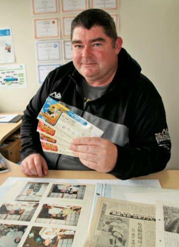W杯大分開催のチケットを手にするディレック・ジョーンズさん。別府時代の写真や本紙のスクラップ記事を大事に残している=3日、NZオークランド市