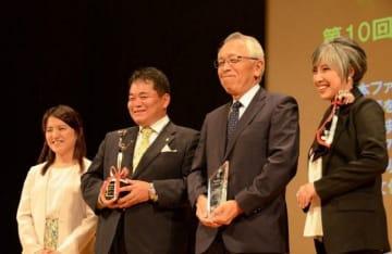 トロフィーを手に笑顔を見せる石田専務理事(左から2人目)=東京
