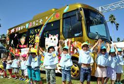 お披露目された金色のバスに大喜びの園児たち=淡路ワールドパークONOKORO