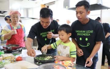 インドネシアの実習生からチョベの使い方を教わる子ども=雲仙市、南串山保健福祉センター
