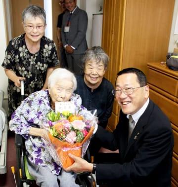 宮本市長(右)から花を受け取る森さん=諫早市、ケアホーム栄田