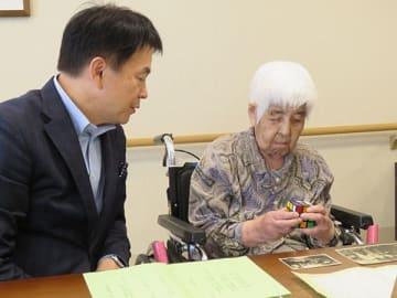 清水勇人市長に得意の六面立体パズルを披露するさいたま市南区の女性最高齢、阪本初子さん=同市南区