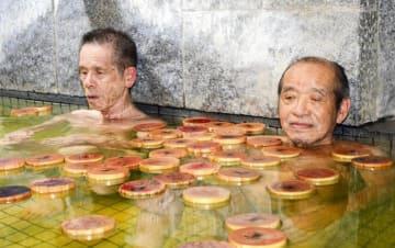 祖父母への感謝の気持ちが書かれたヒノキ片の浮かぶ湯船でリラックスする男性=15日午後、松山市宮田町(撮影・森岡岳夢)