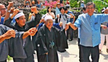 伝統の「トゥンチャー」を歌い、ガーリーを踊る赤山喜介さん(前列右から2人目)と謝花喜一郎副知事(右端)=15日、竹富島