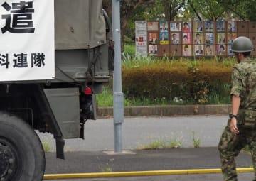 候補者のポスターが張り出された掲示場の近くにも災害派遣の自衛隊車両が止まる=15日、君津市久保