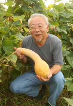 収穫時期を迎えたツルクビカボチャを抱える佐伯和さん=利根町奥山