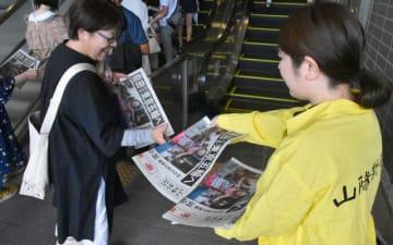 前田選手の快挙を報じる号外を受け取るJR岡山駅の利用者